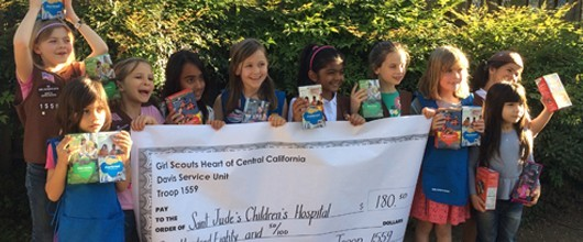 Group of Girl Scouts holding their cookies and a check