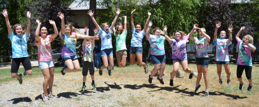 Group of Girl Scouts at Camp Fleming Jumping and Smiling.