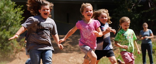 Girls excitedly running in the outdoors.