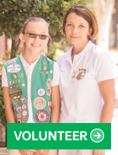 "Girl and troop leader smiling with the caption ""Volunteer"""