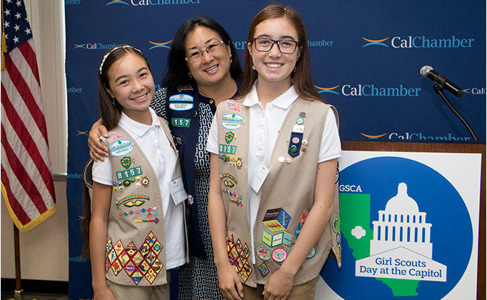 Two Girl Scouts smiling with a Girl Scout Council member.