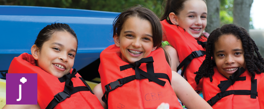 Junior Girl Scouts smiling in life vests